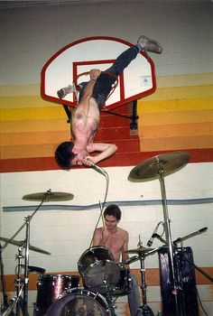 Guy Picciotto falling out of a basketball hoop during a gymnasium concert with his band Fugazi in Philadelphia.