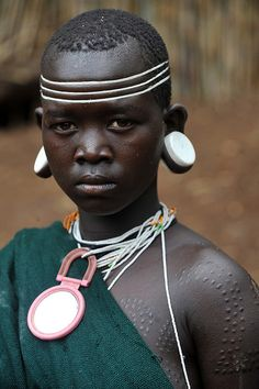 Africa |  Kachipo girl with modern earplugs and scarifications.  The Kachipo are a medium sized tribal group in south-eastern South Sudan, living on the plateau east of Boma, towards the Ethiopian border, some live even in Ethiopia.