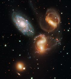 Explanation: The first identified compact galaxy group, Stephan's Quintet  the group are actually locked in a cosmic dance of repeated close encounters. The odd man out is easy to spot, though. The four interacting galaxies (NGC 7319, 7318A, 7318B, and 7317) have an overall yellowish cast and tend to have distorted loops and tails, grown under the influence of disruptive gravitational tides. But the bluish galaxy at the upper left (NGC 7320) is much closer than the others.