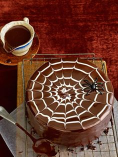 Fill a small piping bag with three to four tablespoons of melted white chocolate, then starting at the center of the top of the cake, pipe the white chocolate in a spiral. Drag a toothpick from the center of the spiral to the cake's edge. Repeat every 1.5 inches to create a web effect.