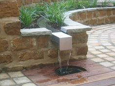 Stainless steel rill in stone wall - Till water features