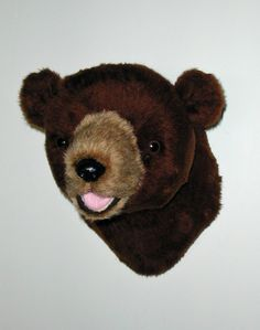 """Plush Brown Bear Head """"Rusty"""" Small Shoulder Mount. Rusty is a soft, short plush cinnamon brown bear. He's perfect for wherever you want to add a playful touch. Everyone loves Rusty. He has a sweet smile that shows just the tip of his little pink tongue. PRODUCT SPECS: Ready to hang. Rusty's depth is 12"""" from nose to wall. Girth at shoulder is 24""""."""