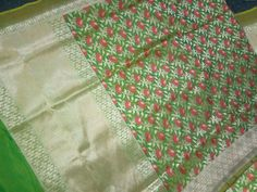 This apple green katan  silk saree with pink roses strewn across the body. The border is zari with a running leaf green edge. Accompanied by a plain apple green blouse, this Banarasi is a story of colors.