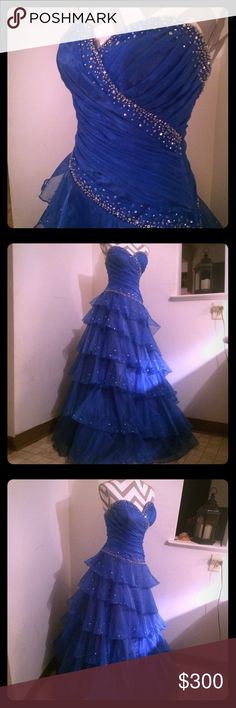 Mystique prom dress blue tulle rhinestones Gorg!!! This prom dress by Mystique is absolutely stunning.  Pictures do not do it justice.  Ballroom shape with large tulle layered skirt covered in rhinestones.  Strapless, back zip up with hook and eye closure.  NO FLAWS. Has not even been tailored.  Very long.  Says size 12, however would fit a size 6.  It was tough to zip up completely on my mannequin which is around a size 6.  Please contact me with any questions. mystique Dresses Prom