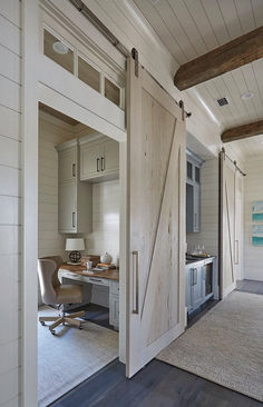 One of the pecky cypress barn door opens to reveal a home office with light gray cabinets suspended over a gray built-in desk with wood top. Barn doors are painted in a custom whitewash stain. ideas Florida Beach House with New Coastal Design Ideas Home Design, Luxury Interior Design, Design Ideas, Blog Design, Interior Modern, Design Projects, Diy Projects, Light Gray Cabinets, Built In Desk