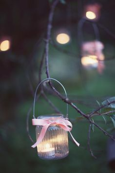 Tea light candles in lanterns hung in old tree