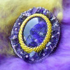 Ametystová+Autorský+šperk.+Brož+je+vyrobena+časově+náročnou+technikou+šitého+šperku+a+korálkové+výšivky.+Použit+je+krásný+ručně+malovaný+skleněný+kabošon+odMalované+kabošonykterý+je+obšívaný+japonskými+korálky+TOHO,+brož+je+doplněna+od+zlomky+polodrahokamu+ametyst,+podšita+je+umělou+semiší+alcantara.