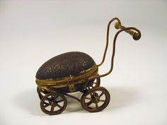Vintage figural egg thimble holder in the form of a baby buggy pram; embossed…