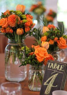 Des roses et des tulipes pour vos centres de table ? Très bonne idée ! Elles ont l'avantage de se trouver facilement dans de nombreuses couleurs différentes. Une bonne manière d'accorder vos centres de tables à votre déco et votre thème. Pour le thème automnal, pas de problème, on mise sur les couleurs chaudes. On reste nature et léger sur le choix du vase. UN vieux pot en verre fera très bien l'affaire pour une décoration discrète et classe.