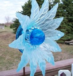 Garden flower suncatcher made from miscellaneous thrift store clear dishes. Flower petal shaped frosted dish with blue glass ball for center.