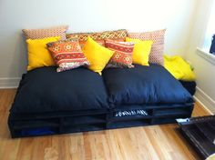 """Being thrifty in med school! Homemade """"couch""""...made the cushions and pillows, wooden pallets as a base can be used for storing blankets, movies etc."""