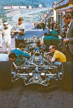 F1 Historic - Jim Clark watching Graham Hill, on Lotus 49, consulting Colin Chapman. Eau Rouge corner in the background.