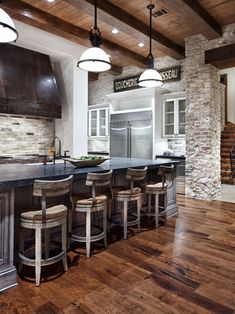 There are many rustic and natural elements used in this kitchen design from brick to wood and barnboard beams. The kitchen Creates a very warm and balanced space. The use of more industrial looking lighting adds a modern twist to this beautiful design!