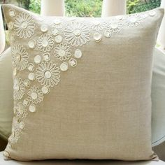 Kussen van linnen of jute met parelmoer knoopjes en witte embroidery