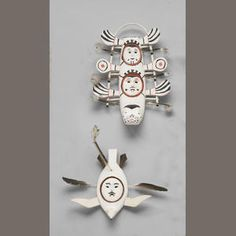 4113  Two Eskimo masks  Both with painted details on white, one depicting a seal with human faces, the other similarly done and rendered as a gull.  length 17 and 12in