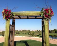 Arch with green draping and red and green floral designs - www.efilasvegas.com - #ceremony #lasvegaswedding