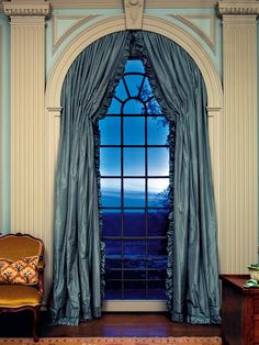 In this living room, dramatic floor-to-ceiling arched windows overlook the nearby river and afford sweeping vistas of the countryside. A luxurious blue silk curtain matches the mood of the window and view.