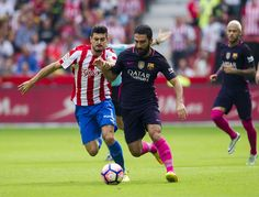 Arda Turan of FC Barcelona duels for the ball with Sergio Alvarez of Real Sporting de Gijon during the La Liga match between Real Sporting de Gijon and FC Barcelona at Estadio El Molinon on September 24, 2016 in Gijon, Spain.