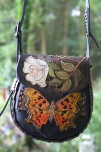 white rose and comma butterfly hand carved and painted on a small dark cocoa brown handstitched bag