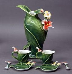 A whimsical ceramic tea set that looks as though its moss green leaves can be peeled away to reveal beautiful blossoms