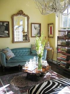 I love this room... The combination of patterns and textures is wonderful. The zebra skin, the oriental rug and the light blue velvet topped off with the knarley wood coffee table. The pale butter cream walls layered with the ornate gold frames and an organic chandelier.