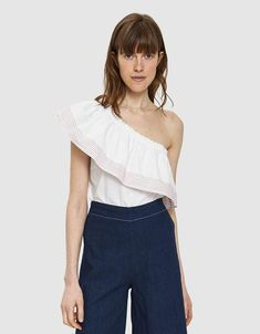 bd5cb441fb4028 Casual top from Farrow in White. One shoulder neckline. Ruffled overlay  with contrast topstitching.