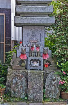 Foxes sacred to Shinto kami Inari, a torii, a Buddhist stone pagoda, and Buddhist figures together at Jōgyō-ji, Kamakura