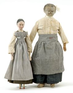 "Lovely gray overdress/pinafore? Germany, mid 19th century, larger doll has carved shoulder head with painted features on original cloth body with period clothing, the second is an all wooden Grodner Tal lady with repainted features, wears original period clothing Size: largest 19"" t."