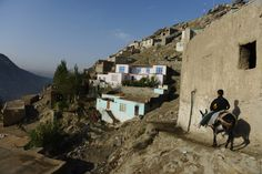 A young resident of the hillside neighborhood of Jamal Mina rides a donkey down to a water collection point high above Kabul. (AFP)