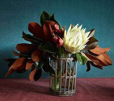 THE ARRANGEMENT | Red amaryllis, a protea flower and Magnolia grandiflora leaves echo the bouquet...