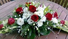 Long and low centrepiece of roses, eustoma, orchids, million star and selection of greens including song of jamaica, monstera, bird's nest, eucalyptus and bear grass.