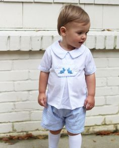 Spring+Tab+Shorts+Set+for+Boy+-+White+pique+shirt+with+light+blue+seersucker+shorts.++Light+blue+seersucker+trim+on+collar,+sleeves,+and+around+each+tab.++Tabs+include:+1+blank+tab+for+optional+monogramming;+2+blue+bunnies+with+fluffy+tails;+embroidered+sailboat;+3+embroidered+crosses.++Great+outfit+for+Easter+that+can+last+throughout+the+spring+and+summer.