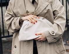 white leather pouch clutch, red nails, trench