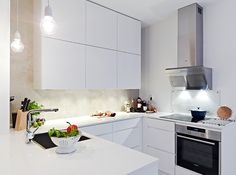 #16. White G-style kitchen with peninsula, upper cabinets go way up to the ceiling, fronts without handles.