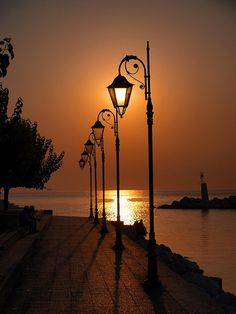 Sunset and the soft glow of the lanterns. Patras, Beautiful Sunset, Beautiful World, Beautiful Places, Pretty Pictures, Cool Photos, Foto Poster, Street Lamp, Belle Photo