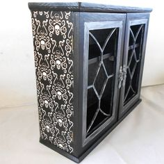 Gothic cabinet  with skull and crossbones theme.