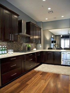 Kitchen: Grey walls, dark wood cabinets, light counter tops, natural flooring, with chrome finishes and appliances.