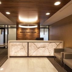 Sophisticated backlit Stone transaction fronts create a grounding presence in the space. Reception Counter Design, Office Reception Design, Spa Interior Design, Hotel Lobby Design, Bussiness Card, Dental Office Design, Hospital Design, Best Kitchen Designs, Office Interiors