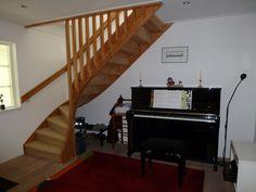 de piano staat onder de trap in een mooie licht hal