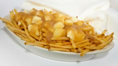 #Poutine is made from a pile of thick-cut French fried potatoes, generously sprinkled with fresh cheese curds and slathered with velvety gravy. #Quebec #Canada