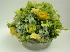 This is a floral arrangement that features roses, hydrangea and dendrobium orchids in a yellow, green and blue color scheme. See our entire selection at www.starflor.com.  To purchase any of our floral selections, as gifts or décor, please call us at 800.520.8999 or visit our e-commerce portal at www.Starbrightnyc.com. This composition of flowers is generally available for same day delivery in New York City (NYC).  LV012