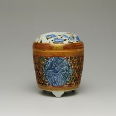 Porcelain incense burner (koro) on three feet and reticulated cover, decorated in underglaze blue and brown and overglaze green and red, the borders gilded with scrolling patterns and paulownia crests: Japan, by Keimei, 1740 - 1780, V.2015.10.6