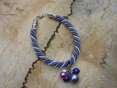 Wrapped bracelet by Gunadesign. Featuring a woven blue multi rope design with colorful beads and wrapped wire.