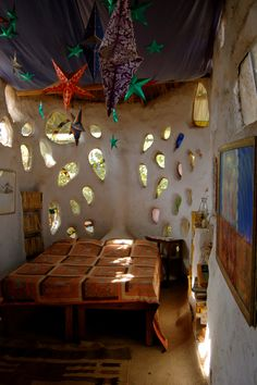 Love this! I think this is an interior view of a cob house. I love the little peek-a-boo glass inserts in the wall!