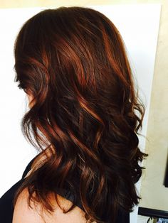 Beautiful brunette with red balayage. Curls are accented beautifully.