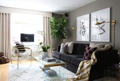Black and white oversized artwork in living room with black sofa and gold wall sconce