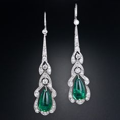 These 2 1/4 inch long and lovely vintage earrings, crafted in platinum in the early 1900s, feature a dreamy pair of lively green cabochon teardrop emeralds weighing 8.00 carats total weight. The emeralds swing back and forth inside elegant diamond frames with graceful curvilinear and characteristically Edwardian outlines.