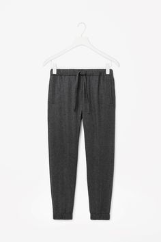 A relaxed, everyday style, these straight-leg trousers are made from wool with a sportswear-inspired drawstring waist and elasticated cuffs. Designed to sit on the waist, they have slanted front pockets and a single pocket on the back.