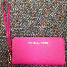 """Michael Kors Wallet Wristlet - Pink Authentic pink Michael Kors slim wallet phone case wristlet. Great condition! Only selling because I want something bigger.   Saffiano leather, Detachable wrist strap with 9"""" drop, Zip around closure gold-tone hardware; logo lettering at front Interior has phone pocket, 5 card slots and ID window.  7"""" W x 3"""" H x 1"""" D Michael Kors Bags Clutches & Wristlets"""