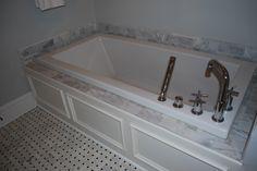 Master Bath - custom designed and built tub panel, white carrara marble tile surround, rectangular extra deep soaking tub, and chrome Roman tub filler faucet and hand shower